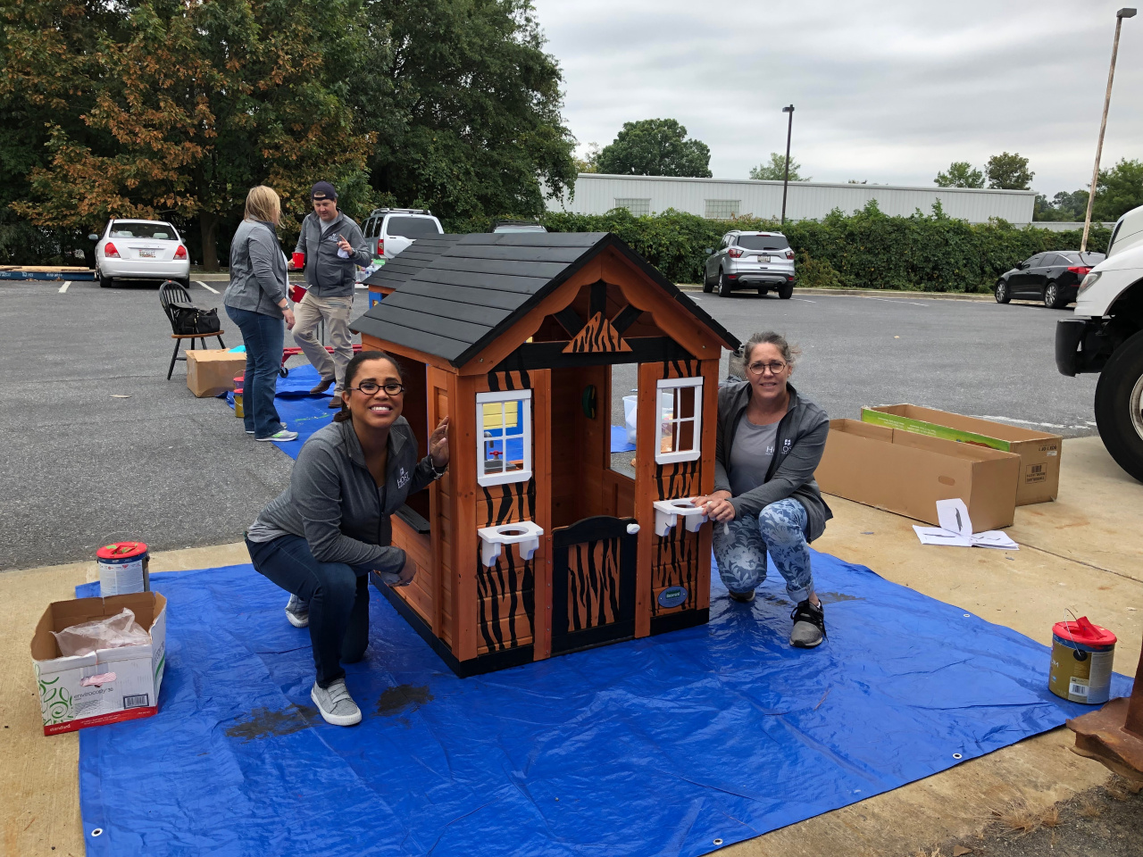 Volunteers construct and paint children's playhouses that are donated to local Habitat families