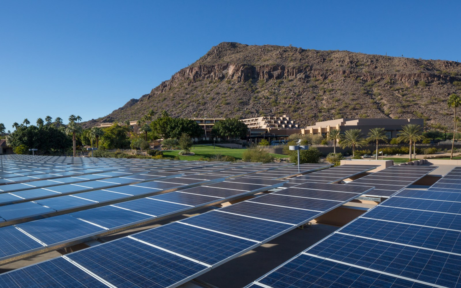 Solar panels on top of parking garage with mountain in background