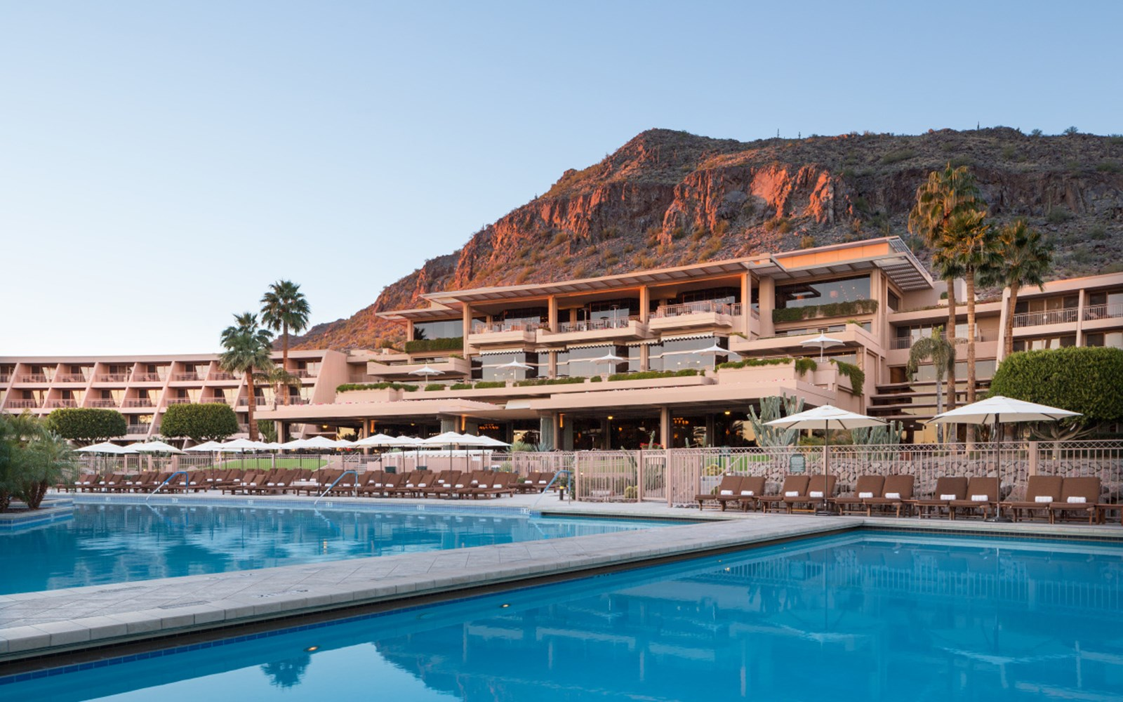 Building that tiers down to pool area with Camelback Mountain in the background