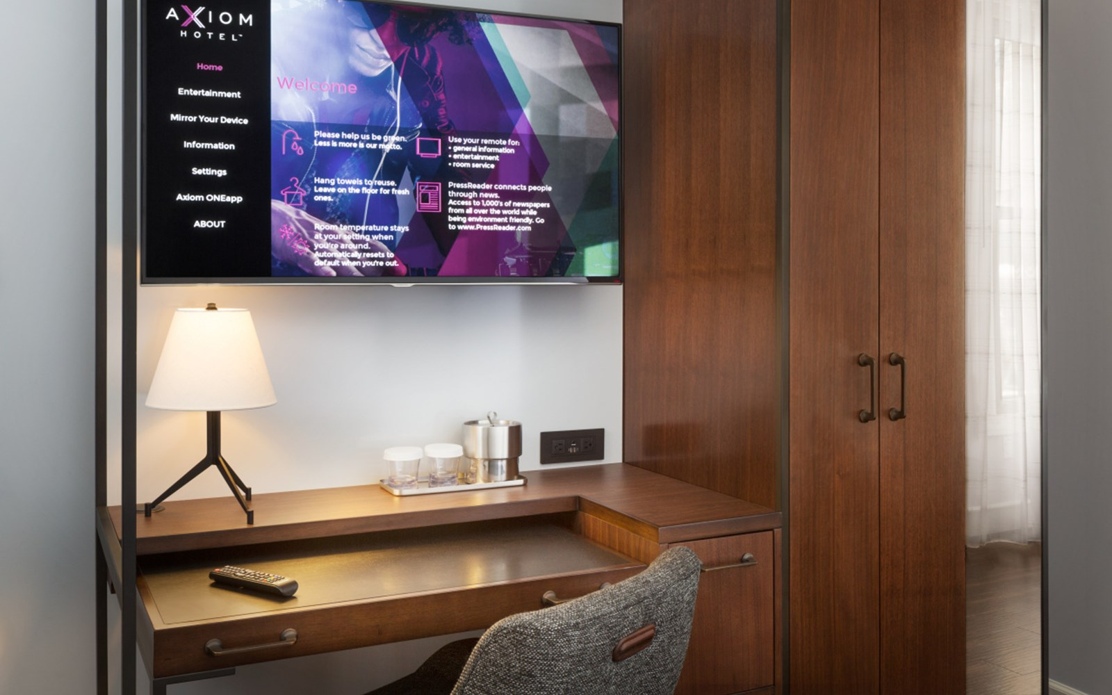 Desk area in guest room with large electronic screen with Axiom Hotel welcome and information