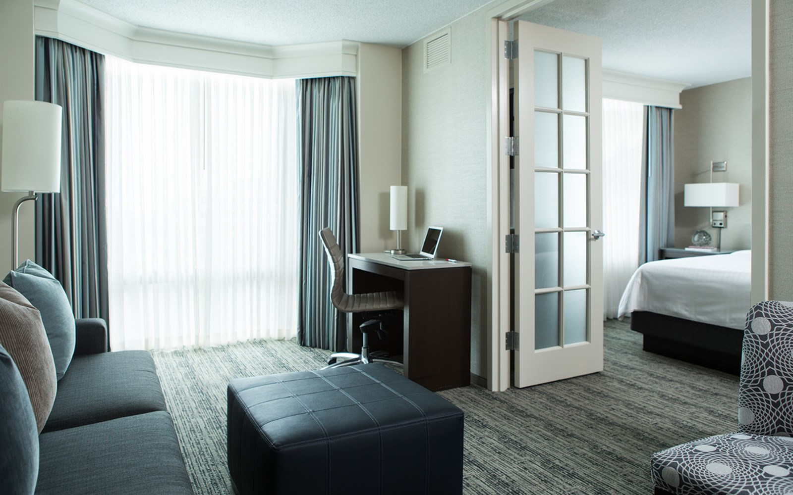 Wide-angled shot of suite living area and king sized bed